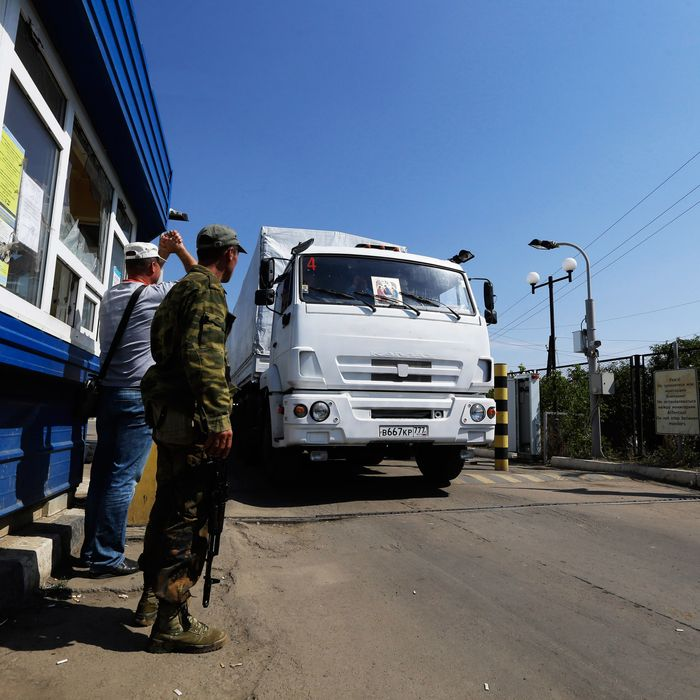 Ukrainian border guards look at the first aid truck as it passes the border post at Izvaryne, eastern Ukraine, Friday, Aug. 22, 2014. The first trucks in a Russian aid convoy crossed into eastern Ukraine on Friday, seemingly without Kiev's approval, after more than a week's delay amid suspicions the mission was being used as a cover for an invasion by Moscow. (AP Photo/Sergei Grits)
