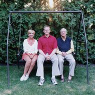 Mature couple and son sitting on lawn swing.