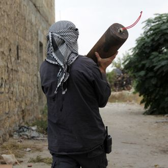 A Syrian rebel carries an improvised explosive device (IED) in the northern city of Aleppo on November 9, 2013. Syrian rebels retook a strategic base in the northern Aleppo province, as shelling killed at least 11 people in nearby Aleppo city, the Syrian Observatory for Human Rights said.