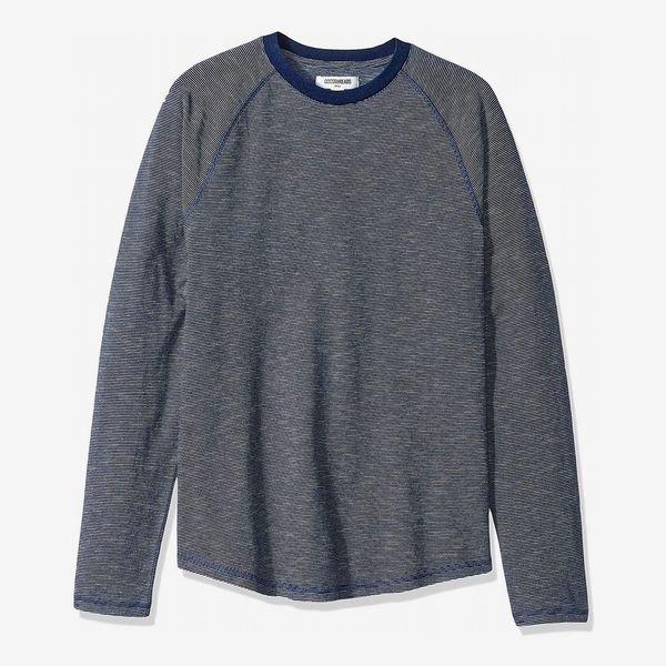 The Goodthreads Men's Long-Sleeve Indigo Raglan T-Shirt with a loose fit in a weathered grey-blue and blue sticking and crewneck collar. 33 Things on Sale You'll Actually Want to Buy: From Adidas to Le Creuset - The Strategist
