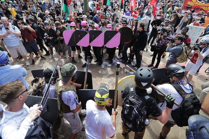"Battle lines form between white nationalists, neo-Nazis, and members of the  ""alt-right,"" and anti-fascist counterprotestors at the entrance to  Emancipation ..."