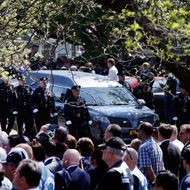 08 May 2015, New York State, USA --- The hearse carrying the remains of New York City police officer Brian Moore escorted by police as it arrives at St. James Roman Catholic church, Friday, May 8, 2015, in Seaford, N.Y. The 25-year-old died Monday, two days after he was shot in Queens. (AP Photo/Mary Altaffer) --- Image by ? Mary Altaffer/AP/Corbis