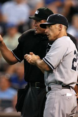 Manager Joe Girardi of the New York Yankees talks with plate umpire Chad Fairchild after Billy Butler's of the Kansas City Royals home run was reviewed in the third inning on August 17, 2011 in Kansas City, Missouri.