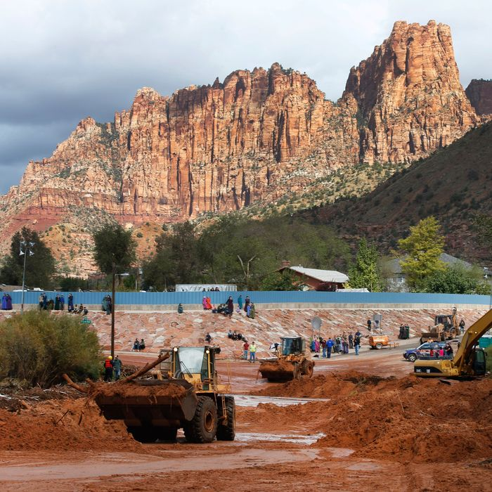 Onlookers watch as construction equipment removes flood debris from Short Creek as it crosses Central Street on September 15, 2015 in Colorado City, Arizona.