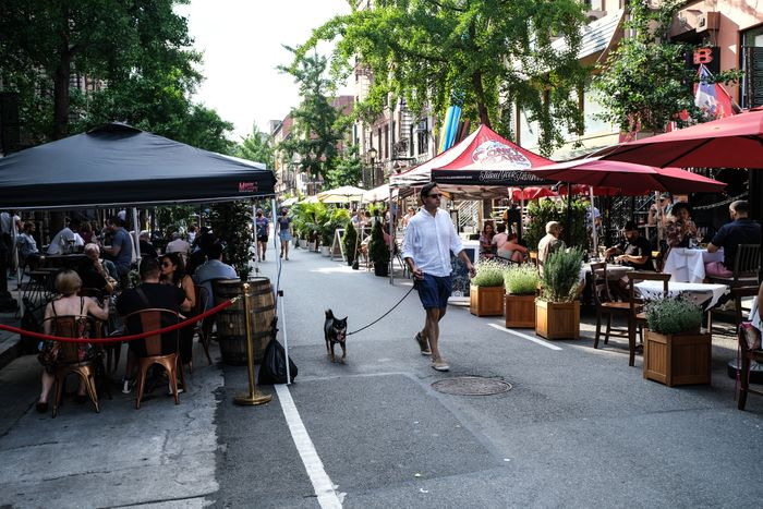 People eating and drinking at outdoor restaurants on a summer day in one of New York City's Open Streets