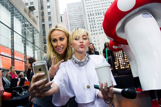 "Miley Cyrus, right, takes a cell phone picture with her mom Tish Cyrus on NBC's ""Today"" show on Monday, Oct. 7, 2013 in New York. (Photo by Charles Sykes/Invision/AP)"
