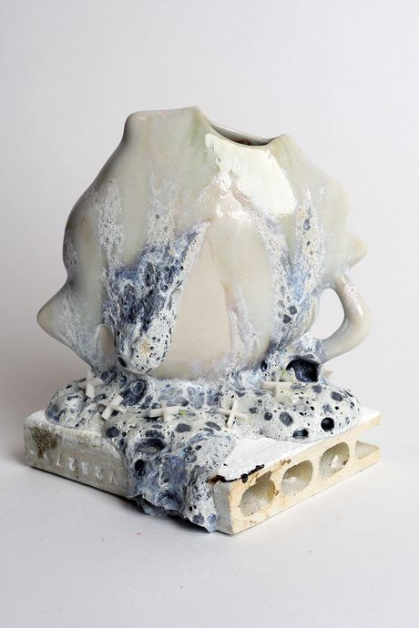 A ceramic vessel with cratery glaze toward its base. the glaze looks like it's slipping off the form