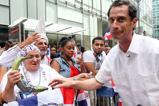 Anthony Weiner, running in the New York Mayors race, right, reacts after sharing a moment with a spectator and her plantains, left, as he takes part in the Dominican Day Parade on New York's Avenue of the Americas Sunday Aug. 11, 2013.  (AP Photo/Tina Fineberg)