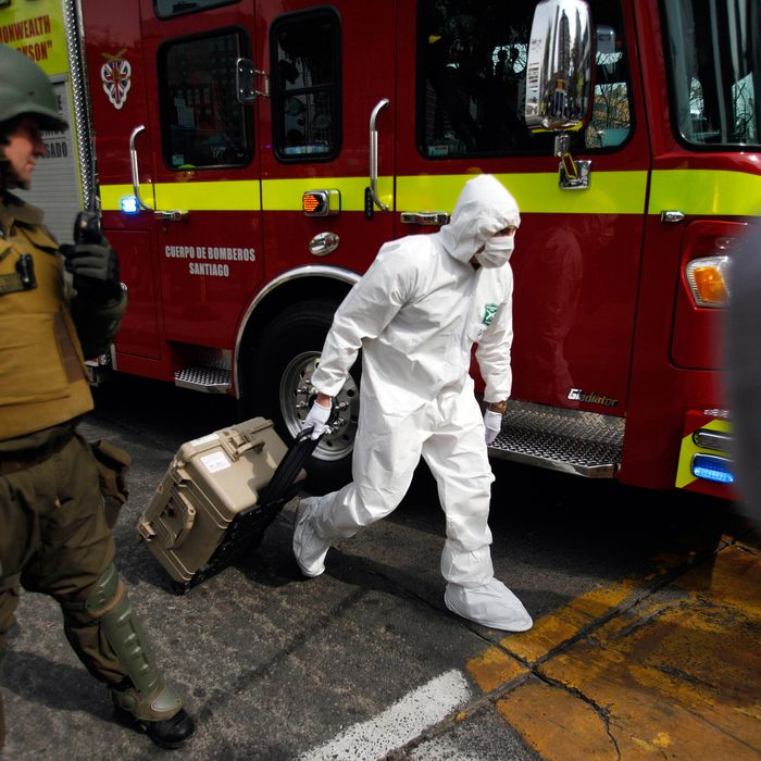 A police forensic expert arrives at a blast site at a subway station in Santiago, Chile, Monday Sept. 8, 2014. A bomb exploded in the Chilean subway station injuring at least seven people, the most damaging in a string of bombs planted around the country's capital this year. (AP Photo/ Luis Hidalgo)