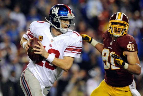 Quarterback Eli Manning #10 of the New York Giants scrambles as he is being chased by Ryan Kerrigan #91 of the Washington Redskins in the third quarter against the Washington Redskins at FedExField on December 3, 2012 in Landover, Maryland.