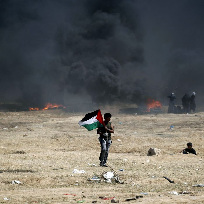A man holds a Palestinian flag during clashes with Israeli forces near the border between the Gaza strip and Israel, east of Gaza City on May 14, 2018, following the the controversial move to Jerusalem of the United States embassy.