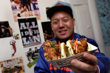 "Eddie Huang, co-owner of Baohaus, holds a pair of  ""The Taiwanese Te-Bao,"" a Taiwanese pork chop with curry seasoning, pickles daikon-carrot, jalapeno, aioli and cilantro in a steamed bun, in the New York restaurant, Friday, Feb. 17, 2012. New York Knicks point guard Jeremy Lin may be hot on the court, but can he sell a drink? How about a sandwich? If the surge in Lin-inspired cocktails and dishes showing up on menus is any indication, it seems some restaurateurs gambling on yes."
