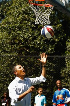 "U.S. President Barack Obama shoots a basketball while participating in a ""Let's Move"" clinic with members of the NBA, WNBA and the Harlem Globetrotters ."