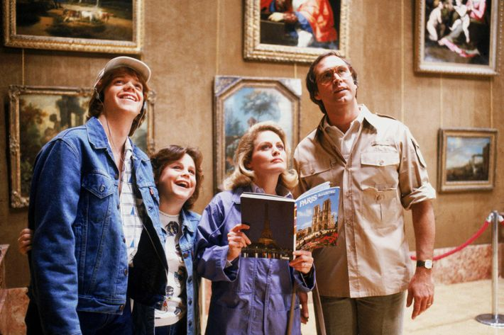 Medium shot of Jason Lively as Russell 'Rusty' Griswald wearing hat, Dana Hill as Audrey Griswald, Beverly D'Angelo as Ellen Griswald holding book and Chevy Chase as Clark Griswald wearing glasses.
