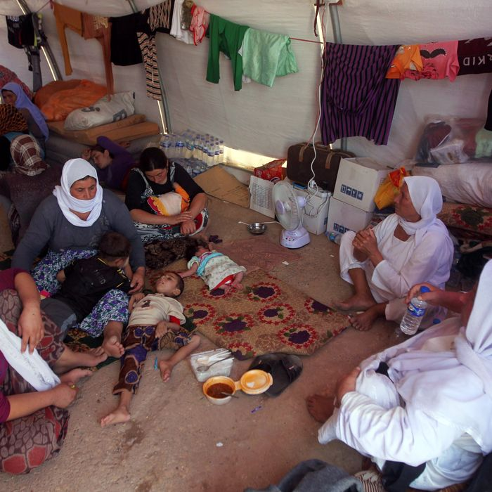 Displaced Iraqi Yazidis, who fled a jihadist onslaught on Sinjar, sit inside a tent after they took refuge at the Bajid Kandala camp in Kurdistan's western Dohuk province, on August 13, 2014. Time is running out for starving Yazidis trapped on an Iraqi mountain as the West ramp up efforts to assist survivors and arm Kurdish forces battling jihadists. AFP PHOTO/AHMAD AL-RUBAYE (Photo credit should read AHMAD AL-RUBAYE/AFP/Getty Images)