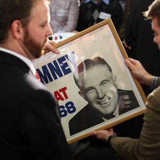 ALBION, MI - FEBRUARY 27: Staff members hold a framed vintage campaign poster of George Romney, father of Republican presidential candidate, former Massachusetts Gov. Mitt Romney, that was given to Mitt Romney during a campaign rally at Caster Concepts on February 27, 2012 in Albion, Michigan. With one day to go before the Michigan and Arizona primaries, Mitt Romney continues to campaign throughout Michigan. (Photo by Justin Sullivan/Getty Images)