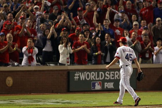 ARLINGTON, TX - OCTOBER 23:  Derek Holland #45 of the Texas Rangers walks off the mound to a standing ovation after being removed in the ninth inning during Game Four of the MLB World Series against the St. Louis Cardinals at Rangers Ballpark in Arlington on October 23, 2011 in Arlington, Texas. The Rangers won 4-0. (Photo by Ezra Shaw/Getty Images)