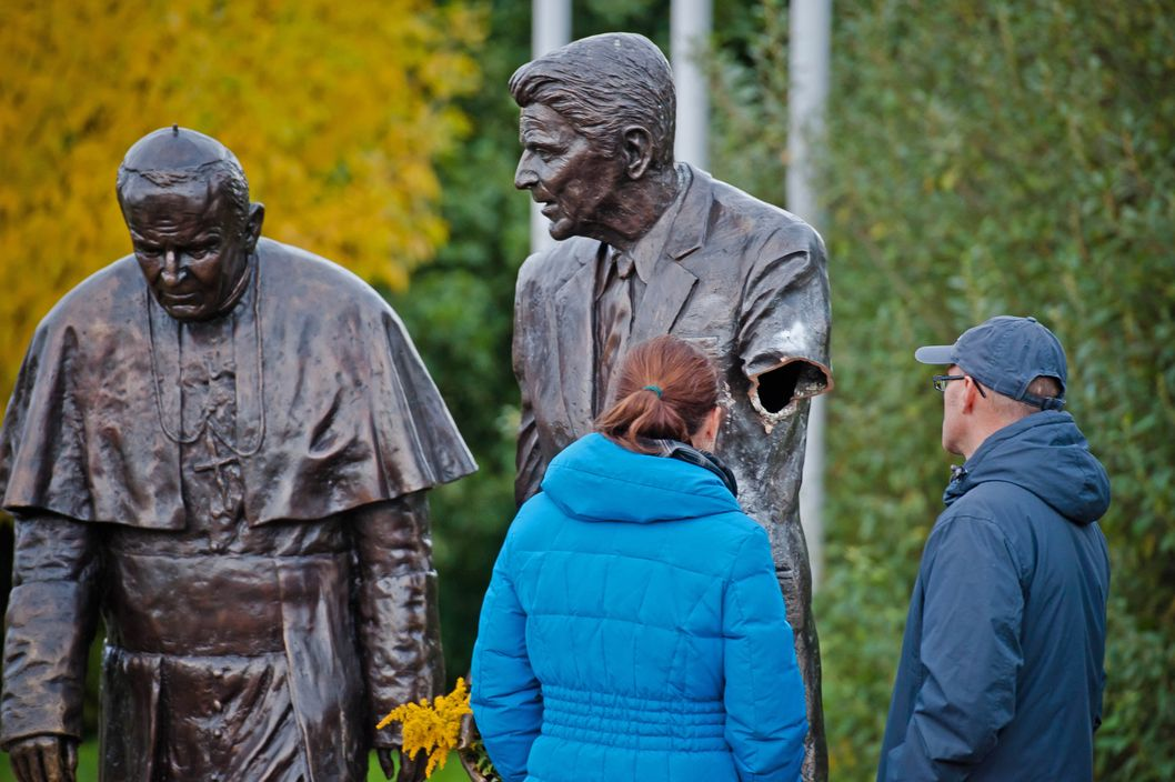 In this Oct. 1, 2013 photo passersbys are seen looking at a former president Ronald Reagan statue with a severed arm in a park in Gdansk, Poland. The bronze statue is a larger than life rendering of Reagan and the Polish born Pope John Paul II, inspired by an AP photograph taken by Scott Stewart during John Paul's visit to the US in 1987 and honor's Reagan's support for Poland's struggle to end communism. The police are searching for the vandal who cut the arm off. (AP Photo/Mateusz Ochocki)