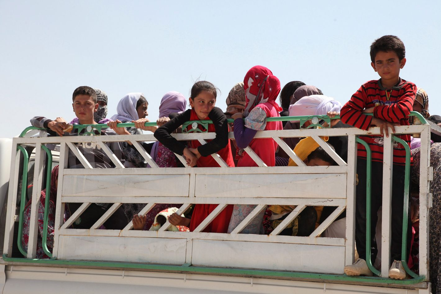 04 Aug 2014, Dohuk, Iraq --- Displaced families from the minority Yazidi sect, fleeing the violence in the Iraqi town of Sinjarl west of Mosul, arrive at Dohuk province, August 4, 2014. Iraq's Prime Minister Nuri al-Maliki ordered his air force for the first time to back Kurdish forces against Islamic State fighters after the Sunni militants made another dramatic push through the north, state television reported on Monday. REUTERS/Ari Jala (IRAQ - Tags: CIVIL UNREST POLITICS) --- Image by ? STRINGER/IRAQ/Reuters/Corbis