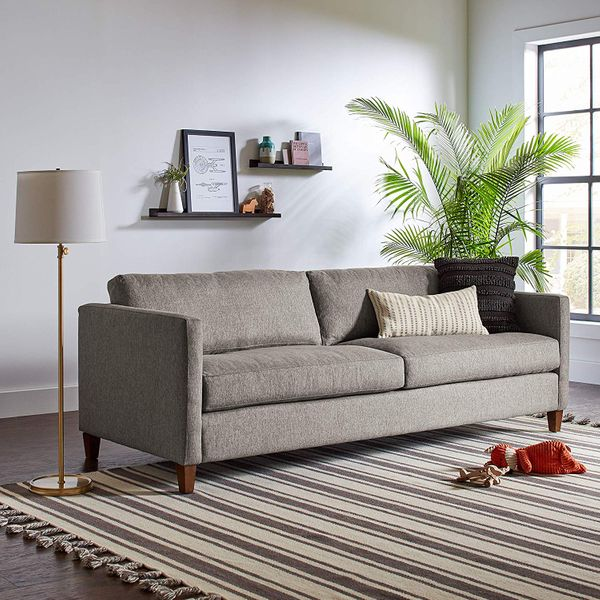 A brass Wayfair floor lamp with a cream linen lampshade next to a gray couch, a striped rug, and two shelves. The Strategist - Very Tasteful Lamps from Amazon's Rivet and Stone and Beam Are on Sale