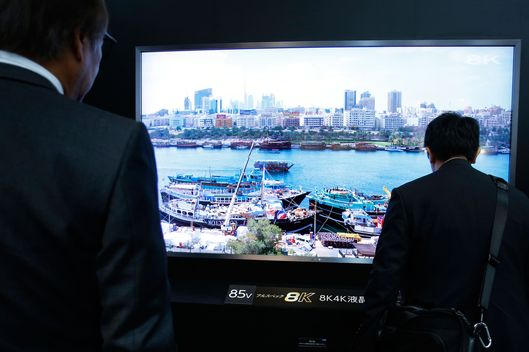 Attendees examine a Sharp Corp. 85-inch 8K full-spec liquid crystal display (LCD) television at the Cutting-Edge IT & Electronics Comprehensive Exhibition (CEATEC) in Chiba, Japan, on Tuesday, Oct. 7, 2014. Sharp President Kozo Takahashi has been able to focus on cutting fixed costs by 167 billion yen ($1.5 billion) in the past two years and shifting its product mix to smaller panels to supply Chinese smartphone makers.  Photographer: Kiyoshi Ota/Bloomberg via Getty Images