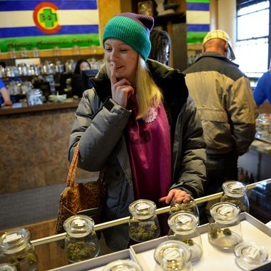 "DENVER, CO. - JANUARY 02: Kristin Brinckerhoff ponders the selection of marijuana  at 3D Cannabis Center in Denver, CO January 02, 2014. Kristin said she waited a day to buy marijuana, ""I just knew the lines were going to be out of control. I think it's amazing, I grew up in Virginia where it's really frowned upon... I'm young but I never thought I'd see the day,"" she said.  The retail marijuana store opened on January 1, 2014 when Colorado became the first place anywhere in the world to allow legal marijuana sales to anybody over 21 for any purpose. (Photo By Craig F. Walker / The Denver Post)"