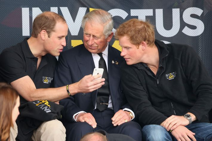 Prince William, Prince Charles and Prince Harry using cell phone.