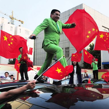 "This picture taken on October 10, 2012 shows Chinese billionaire and philanthropist Chen Guangbiao jumping on the roofs of the new cars which he bought costing five million yuan (795,000 USD) in Beijing as presents to the 43 owners of Japanese cars that were damaged last month during the nationwide anti-Japan protests that were fueled by Japan's ""purchase"" of the Diaoyu Islands, also known as the Senkaku islands in Japan. The dispute over the uninhabited island chain, which has rumbled for decades, flared in August and September with landings by nationalists from both sides and the subsequent nationalisation of the islands by Tokyo."