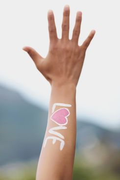 LOVE tattooed on woman's hand --- Image by ? Moment/cultura/Corbis
