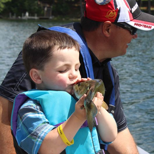 In this photo made Wednesday, June 26, 2013 in Nevis , Minn., Bobby Tufts, the 4-year-old mayor of Dorset, Minn., kisses a fish that his guide, Jason Durham, caught on Lake Belle Taine. The fish, the first was released. Bobby was only 3 when he won election last year as mayor of Dorset (population 22 to 28, depending on whether the minister and his family are in town). Dorset, which bills itself as the Restaurant Capital of the World, has no formal city government.