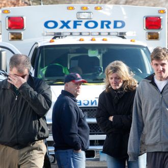 Relatives react outside Sandy Hook Elementary School following a shooting in Newtown, Connecticut, December 14, 2012.