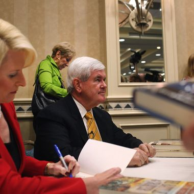 Republican presidential hopeful and former Speaker of the House Newt Gingrich and his wife Callista sign books after speaking at a Hilton Hotel on November 25, 2011 in Naples, Florida.