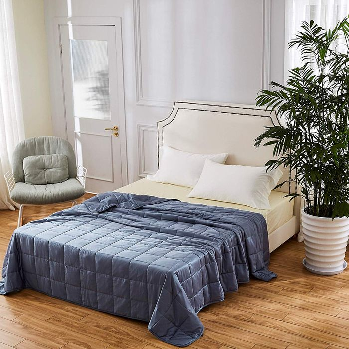 blue weighted blanket on top of bed with yellow sheets and white pillows inside a bedroom - strategist best weighted blanket