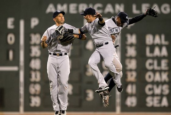 BOSTON - APRIL 21: New York Yankees left fielder Raul Ibanez (#27), New York Yankees center fielder Curtis Granderson (#14), and New York Yankees right fielder Nick Swisher (33) celebrate the win over the Boston Red Sox.   The Boston Red Sox took on the New York Yankees at Fenway Park. (Photo by Barry Chin/The Boston Globe via Getty Images).