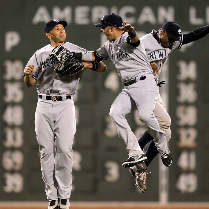 New York Yankees left fielder Raul Ibanez (#27), New York Yankees center fielder Curtis Granderson (#14), and New York Yankees right fielder Nick Swisher (33) celebrate the win over the Boston Red Sox. The Boston Red Sox took on the New York Yankees at Fenway Park.