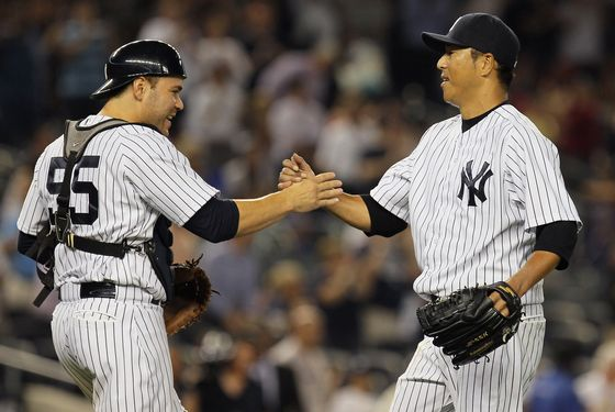 NEW YORK, NY - AUGUST 14:  Hiroki Kuroda #18 of the New York Yankees celebrates with Russell Martin #55 after pitching a complete game shutout against the Texas Rangers at Yankee Stadium on August 14, 2012 in the Bronx borough of New York City. Yankees defeated the Rangers 3-0.  (Photo by Mike Stobe/Getty Images)