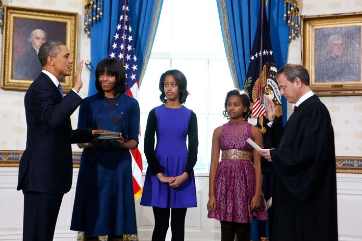 US President Barack Obama (L) takes the oath of office from US Supreme Court Chief Justice John Roberts as first lady Michelle Obama holds the bible and their daughters Malia (C) and Sasha (2nd R) look on in the Blue Room of the White House in Washington on January 20, 2013.