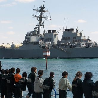 A file picture taken on March 16, 2009, shows Egyptians watching guided missile destroyer USS Mahan crossing the Suez Canal near Egypt's port city of Ismailia as it travels back to the US. USS Mahan left the Mediterranean Sea on September 3, 2013 while a battle group of warships led by the aircraft carrier USS Nimitz is on its way to the Red Sea from the Indian Ocean, an official said, as the US prepares itself for possible military action in Syria following an alleged chemical weapons attack on the outskirts of Damascus. AFP PHOTO / STR (Photo credit should read STR/AFP/Getty Images)