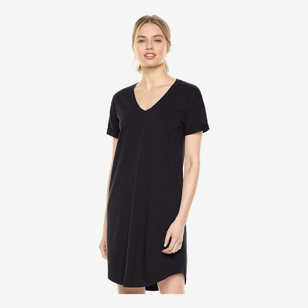 A model wearing the short Daily Ritual Women's Lived-in Cotton Roll-Sleeve V-Neck T-Shirt Dress in black. 33 Things on Sale You'll Actually Want to Buy: From Adidas to Le Creuset - The Strategist