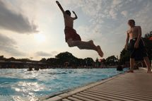A boy jumps as people bathe on opening day of the newly renovated McCarren Park Pool on June 28, 2012 in the Brooklyn borough of New York City. The historic 37,000 square-foot pool had been closed since 1983 but has been rejuvenated by a $50 million restoration. New York City public swimming pools opened today for the summer.