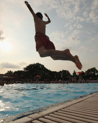 NEW YORK, NY - JUNE 28: A boy jumps as people bathe on opening day of the newly renovated McCarren Park Pool on June 28, 2012 in the Brooklyn borough of New York City. The historic 37,000 square-foot pool had been closed since 1983 but has been rejuvenated by a $50 million restoration. New York City public swimming pools opened today for the summer. (Photo by Mario Tama/Getty Images)