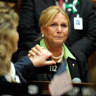 State Rep. DebraLee Hovey, R-112 district, including Newtown, grabs the hand of colleague Rep. Laura Hoydick, R-Stratford, left, after speaking at a memorial service for the victims of the Sandy Hook Elementary School shooting before the House of Representatives and Senate meet for special session the state Capitol in Hartford, Conn., Wednesday, Dec. 19, 2012.