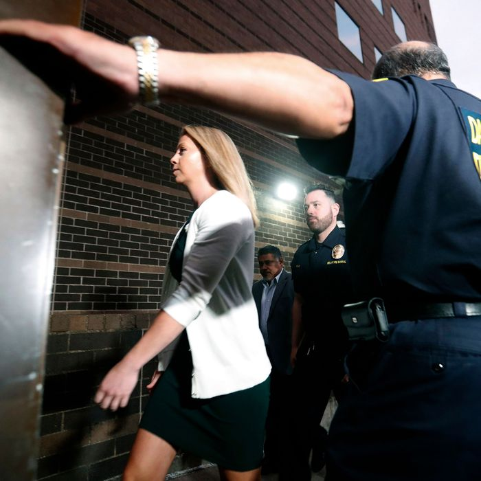 Amber Guyger, center, walks flanked by security while arriving for her murder trial at the Frank Crowley Courthouse in downtown Dallas.