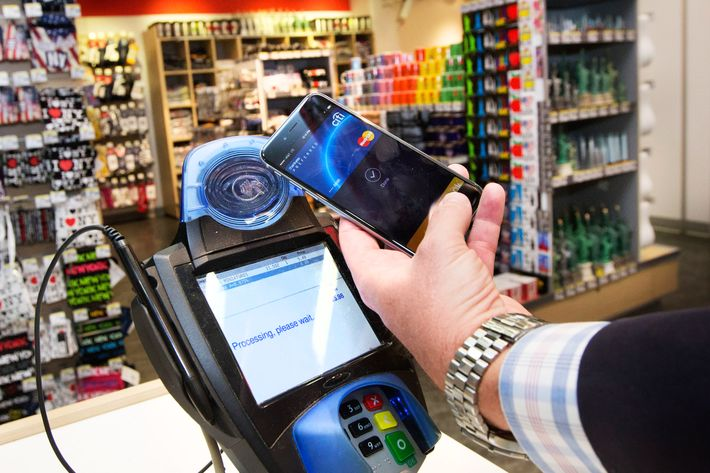 IMAGE DISTRIBUTED FOR MASTERCARD - A customer makes a purchase with a MasterCard using Apple Pay on the iPhone 6 at Walgreens in Times Square, Monday, Oct. 20, 2014, in New York. The service launched Monday. (John Minchillo/AP Images for MasterCard)