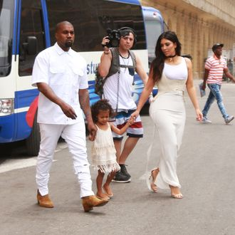 Kim Kardashian dressed in white shows her style as Cuban fans literally swarm their classic car to get photos of her and her sisters and their kids on 1st trip to Cuba with Kanye West