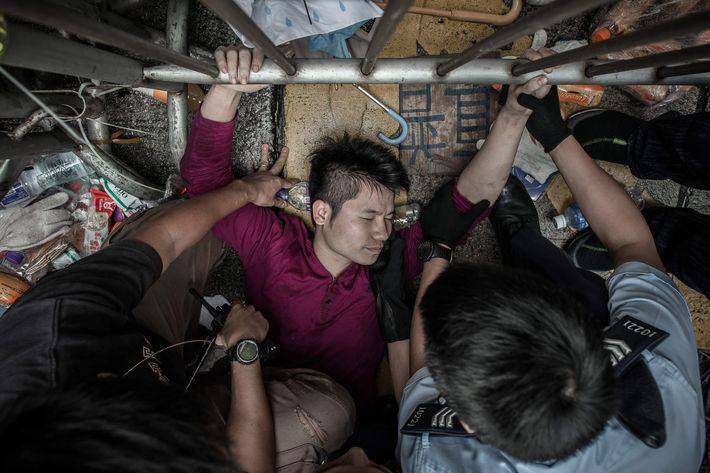 Policemen try to get a man to let go of a fence guarded by pro-democracy demonstrators in an occupied area of Hong Kong on October 3, 2014. Pro-democracy protesters clashed with opposition groups in two of Hong Kong's busiest shopping districts on October 3, with police stepping in to try to calm the chaos. AFP PHOTO / Philippe Lopez        (Photo credit should read PHILIPPE LOPEZ/AFP/Getty Images)
