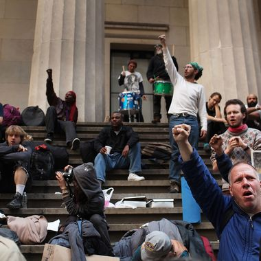 NEW YORK, NY - APRIL 16:  Members of Occupy Wall Street gather on the steps of Federal Hall after being evicted from the sidewalk early in the morning where they had been sleeping on April 16, 2012 in New York City. As temperatures warm, members of the global protest movement have reasserted their commitment to finding a permanent presence in the financial district following their eviction from Zucotti Park last November in a dramatic police raid.  (Photo by Spencer Platt/Getty Images)