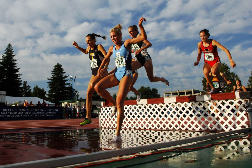 Ebba Stenback of Toledo (522) and Cassie King of North Carolina (328) negotiate the water jump in the women's steeplechase in the NCAA Track & Field Championships