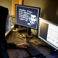 A masked hacker, part of the Anonymous group, hacks the French presidential Elysee Palace website on January 20, 2012 near the eastern city of Lyon. Anonymous, which briefly knocked the FBI and Justice Department websites offline in retaliation for the US shutdown of file-sharing site Megaupload, is a shadowy group of international hackers with no central hierarchy. On the left screen, an Occupy mask is seen. AFP PHOTO / JEAN-PHILIPPE KSIAZEK (Photo credit should read JEAN-PHILIPPE KSIAZEK/AFP/Getty Images)