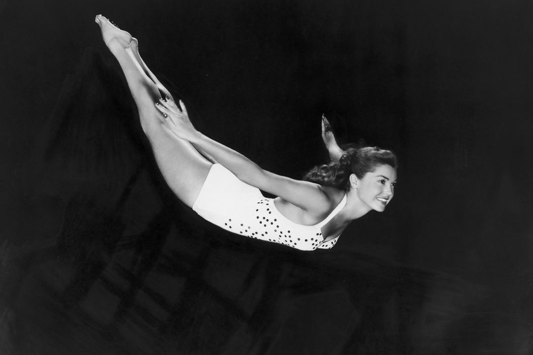 circa 1945:  Portrait of aquatic American actor and swimmer Esther Williams diving through the air in a one-piece swimsuit.  (Photo by Hulton Archive/Getty Images)